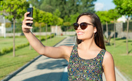 Pretty girl smiling and taking selfie in park. Pretty girl wearing sunglasses smiling and taking selfie outside in park in sunlight Stock Photos