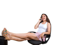 Pretty girl smiling with telephone in office chair Stock Photos