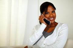 Pretty girl smiling at you while speaking on phone Royalty Free Stock Photography