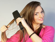 PRETTY GIRL SMOOTHING HER HAIR Stock Photos