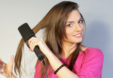 PRETTY GIRL SMOOTHING HER HAIR Stock Photography