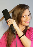 PRETTY GIRL SMOOTHING HER HAIR Royalty Free Stock Images