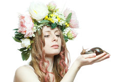 Pretty girl with snail and flower crown on head. Pretty girl with snail in hand and flower crown on head isolated in white background Royalty Free Stock Photography