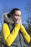 Pretty girl sneezing outdoors Royalty Free Stock Photography