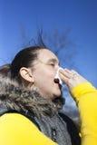 Pretty girl sneezing outdoors Stock Photo