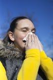 Pretty girl sneezing outdoors Stock Photos