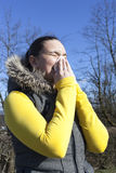 Pretty girl sneezing outdoors Royalty Free Stock Image