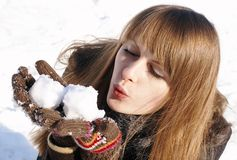 Pretty girl with snowballs. Young pretty girl is blowing snowballs royalty free stock photo