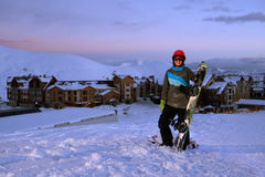 Pretty Girl snowboarder stands on front of hotel ski resort Stock Photo