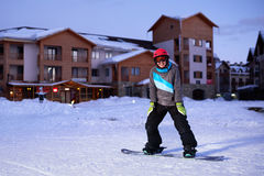 Pretty Girl snowboarder stands on front of hotel ski resort Stock Images