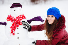 Pretty girl with snowman Stock Photography