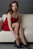 Pretty girl on sofa. Beautiful girl in a red dress stock image