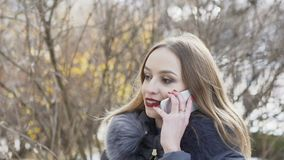 Pretty girl speaking on the phone on winter street. Slowly.  stock video