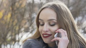 Pretty girl speaking on the phone on winter street. Slowly.  stock video footage