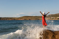 Pretty girl splashing by ocean wave Stock Photos