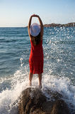 Pretty girl splashing by ocean wave Stock Photography