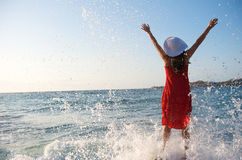Pretty girl splashing by ocean wave Stock Image