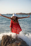 Pretty girl splashing by ocean wave Royalty Free Stock Images