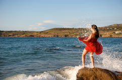 Pretty girl splashing by ocean wave Royalty Free Stock Photography