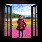 Pretty girl, spring awaking. Chinese little girl in traditional red dress standing on a wood window, holding a flower on her face. Colorful flowers field royalty free stock photo