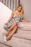 Pretty Girl on Stairs. Beautiful Asian woman in a dress and heals sitting on a staircase Royalty Free Stock Photo
