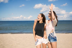 Pretty girl standing on beach with her friend waving and laughin Stock Image
