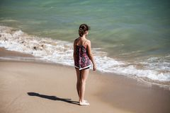 A pretty girl standing  on the beach and looking far into the sea, soft fockus royalty free stock photo