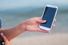 Pretty girl standing on the beach near the sea with smarphone In Stock Photo