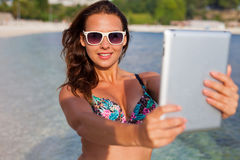 Pretty girl standing on the beach and taking selfie by her table stock photography