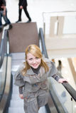 Pretty girl standing on escalator. And moving up Stock Photos
