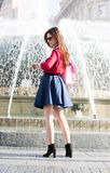 Pretty girl is standing in front of a fountain looking the time. Royalty Free Stock Photography