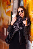 Pretty girl standing in front of wall with cup of coffee Royalty Free Stock Images