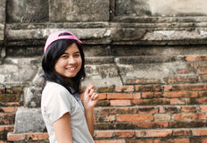 Pretty girl standing near brick wall background Royalty Free Stock Images