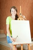 Pretty girl   standing  near easel Stock Photo