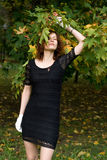 Pretty girl standing near maple tree Royalty Free Stock Photography