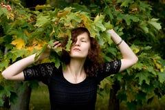 Pretty girl standing near maple tree Stock Photography
