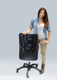 Pretty girl standing next to an office chair Stock Image