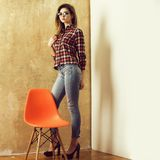 Pretty girl standing at orange chair. Interior and furniture. Pretty girl or woman, fashion model, with stylish, long hair in eyeglasses, red plaid shirt, jeans stock images