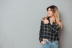 Pretty girl standing and pointing finger away at copy space royalty free stock image