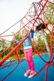 Pretty girl standing on red net of playground Stock Photo
