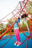 Pretty girl standing on red net of playground Stock Photo