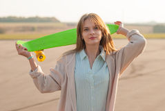 Pretty girl standing with a skateboard Royalty Free Stock Photography