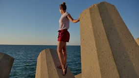 Pretty girl standing on stony blocks looking at the sea stock video