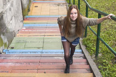 Pretty girl on the stone steps in the city. Royalty Free Stock Photography