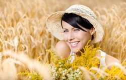 Pretty girl in straw hat against rye field Royalty Free Stock Photography