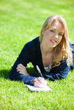 Pretty girl studying on a green meadow Royalty Free Stock Photo
