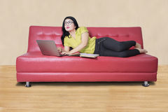 Pretty girl studying with laptop on sofa Royalty Free Stock Image