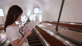 Pretty girl in subway. Young woman with long dark hair looking at a map on an escalator going up. Pretty girl in subway. Young woman with long dark hair in a stock video footage