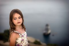 Pretty girl in summer dress with wet hair stands thoughtfully by the sea stock images