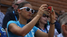 Pretty girl in sun glasses takes photos on tribune closeup stock video footage